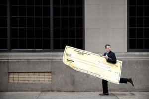 Businessman running along sidewalk with oversized cheque
